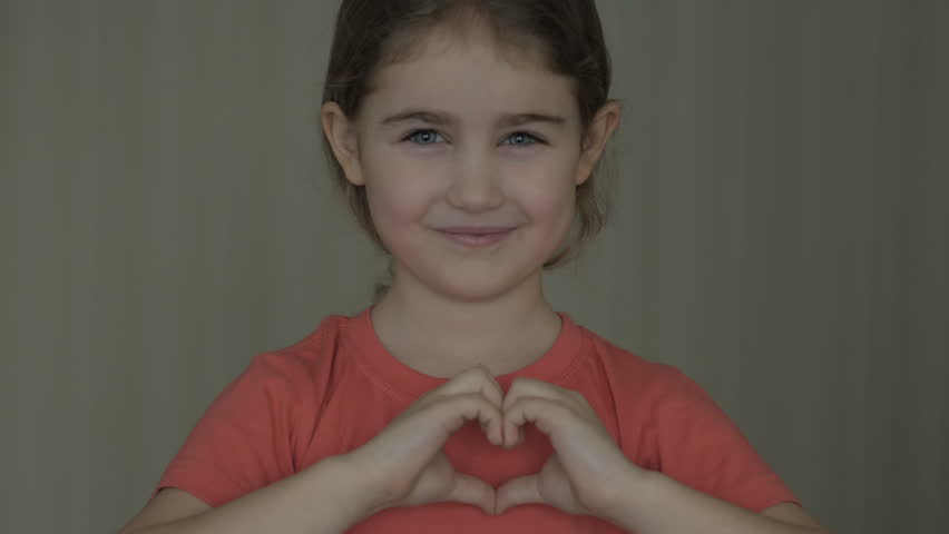 Cute little girl making a heart with her hands and smiling. Young beautiful girl smiling in love showing heart symbol and shape with hands. Romantic concept. Mothers Day.  | Shutterstock HD Video #1025114270