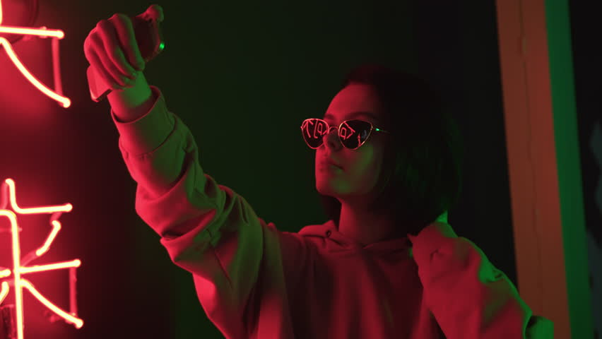 Trendy cute girl blogger in sunglasses taking selfie photo or video using smartphone. Attractive brunette young woman looks at herself with mobile phone and touching her short hair. Red neon light | Shutterstock HD Video #1025122397