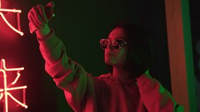 Trendy cute girl blogger in sunglasses taking selfie photo or video using smartphone. Attractive brunette young woman looks at herself with mobile phone and touching her short hair. Red neon light