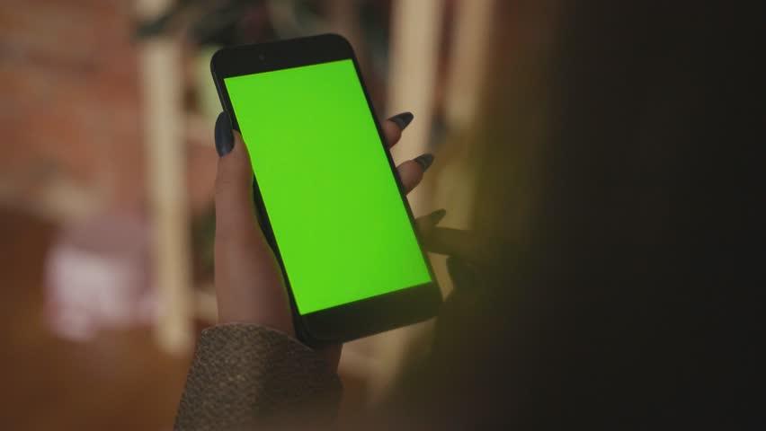 Beautiful girl holding a smartphone in the hands of a green screen green screen. | Shutterstock HD Video #1025123879