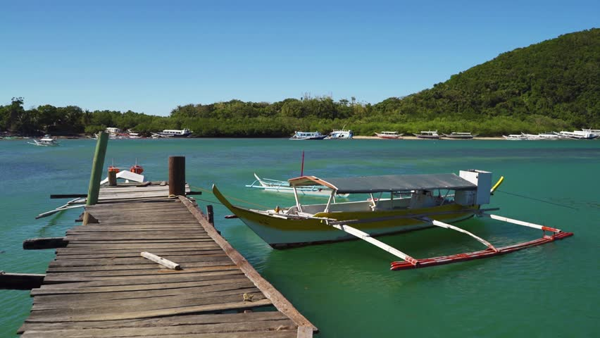 Filipino Bangka Boats Attached to a Wooden Pier in Puerto Gallera, Philippines | Shutterstock HD Video #1025127482