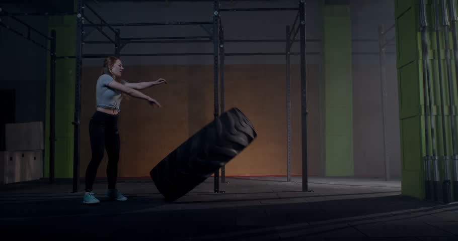 Caucasian female athlete flipping large tire in a gym. Cross workout training. 4K UHD | Shutterstock HD Video #1025135516