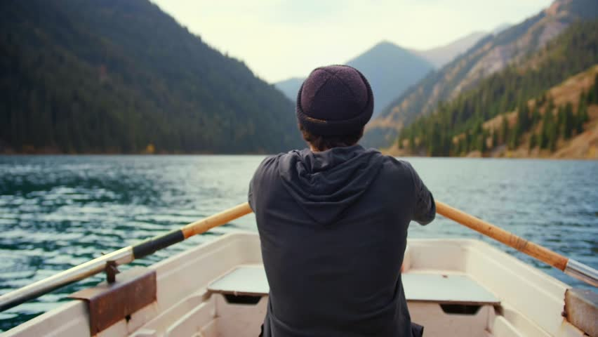 Hipster man is paddling on the small boat or canoe in middle of lake and green pine woods forest mountains in nature of Asia in awaited active vacations holidays Feel calm relax desconection and sport | Shutterstock HD Video #1025138633