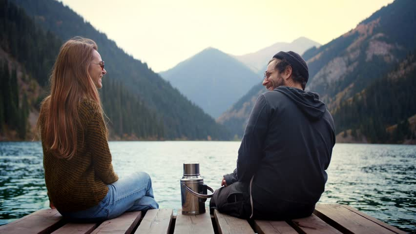 Beautiful happy real romantic couple of match man and woman friends in love on first date in nature having fun smiling or laughing give a high five and sitting on wooden bridge of green mountains lake | Shutterstock HD Video #1025138693