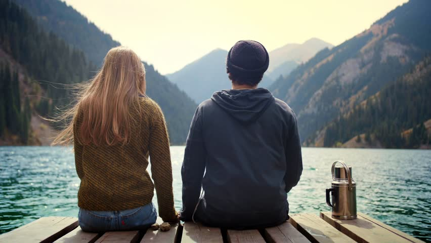 Beautiful real romantic couple of man and woman on first date in nature holding hands look to each other and kiss sitting on wooden bridge of mountains lake observing view and feel love calm happiness Royalty-Free Stock Footage #1025138708