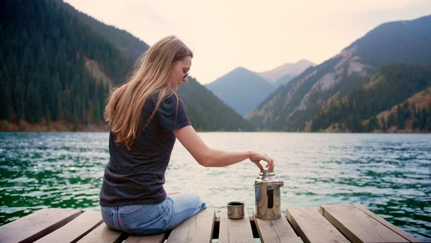Beautiful female traveler sitting on wooden bridge of lake green mountains in connection with nature pouring drinking and enjoying taste of hot tea or thermos beverage Feel calm state of mind in relax | Shutterstock HD Video #1025138735