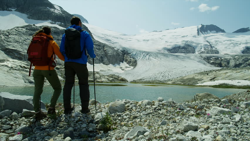 Active people leisure hiking in extreme high mountain terrain relaxing by ice glacier in bright summer sunlight British Columbia RED MONSTRO | Shutterstock HD Video #1025147018