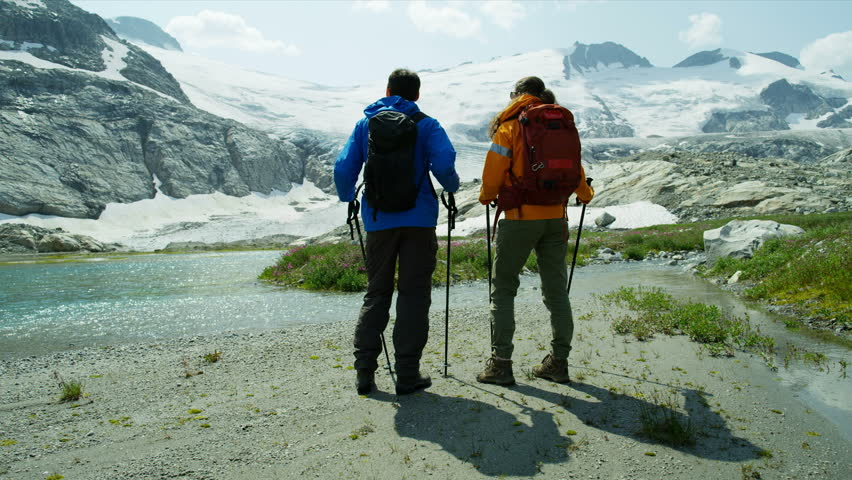 Lake view Heli hikers male and female young Caucasian travelers hiking in scenic mountains near ice glacier RED MONSTRO | Shutterstock HD Video #1025147144