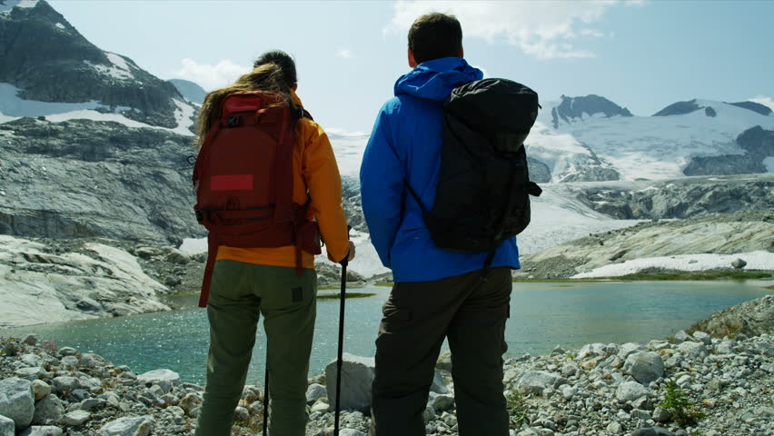 Heli hikers Caucasian male and female active adventure hiking near remote outdoor glacial lake and ice glacier RED MONSTRO | Shutterstock HD Video #1025147201