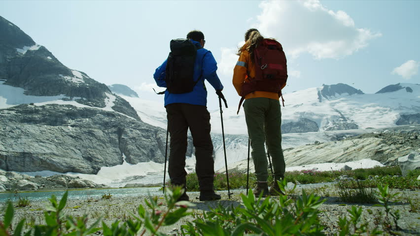 Heli hikers Caucasian male and female active adventure hiking near remote outdoor glacial lake and ice glacier summer RED MONSTRO | Shutterstock HD Video #1025147204