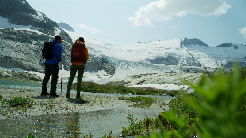 Lake view Heli hikers male and female young Caucasian travelers hiking in scenic mountains near ice glacier RED MONSTRO | Shutterstock HD Video #1025147207