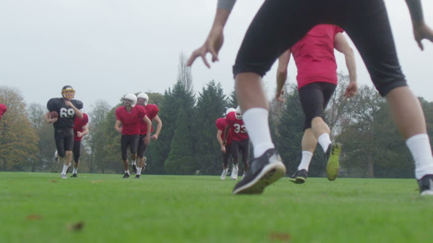 American football player running with the ball, trying to avoid opposing players #10251590