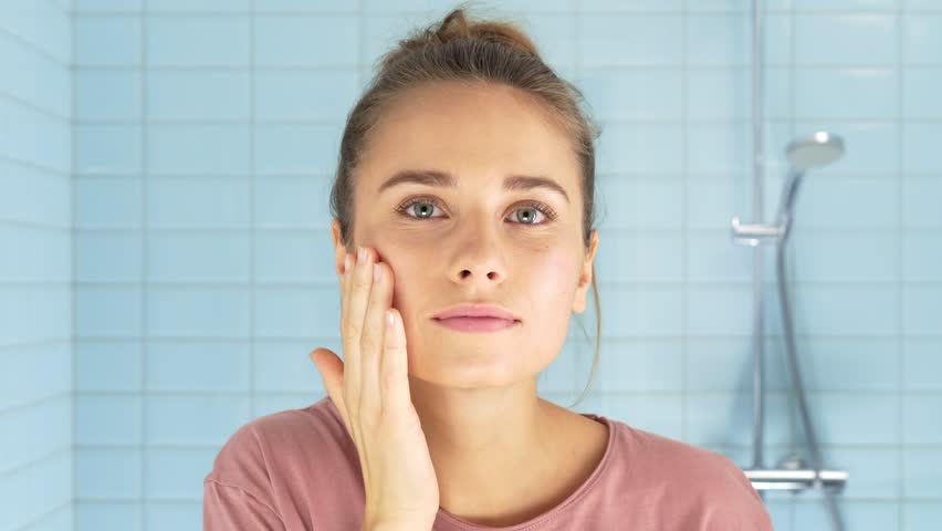 Gorgeous woman applying moisturizing lotion on her face   Shutterstock HD Video #1025160452