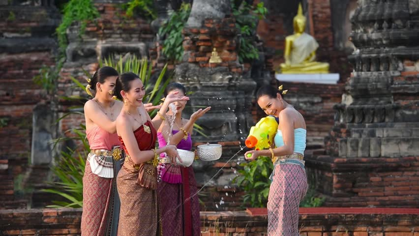 Songkran festival Thailand culture. Asia woman with Thai traditional culture dress play water in songkran festival in the temple of Thialand. | Shutterstock HD Video #1025174618