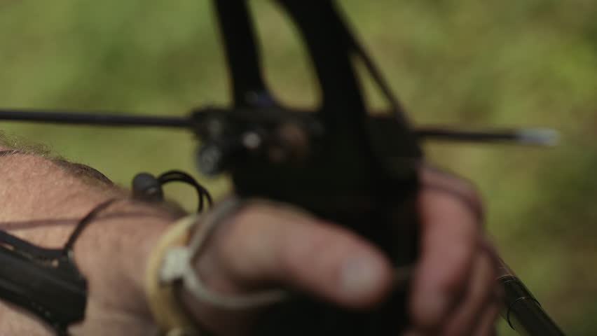 Close-up. Man Shoots An Arrow From A Bow.
