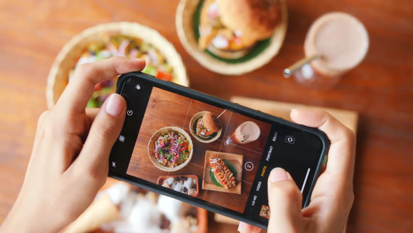 Female Taking Photo of Fast Food Using Mobile Phone in Vegan Restaurant. 4K Slowmotion Flatlay Food Photography on Wooden Table in American Diner. Bali, Indonesia. | Shutterstock HD Video #1025179151
