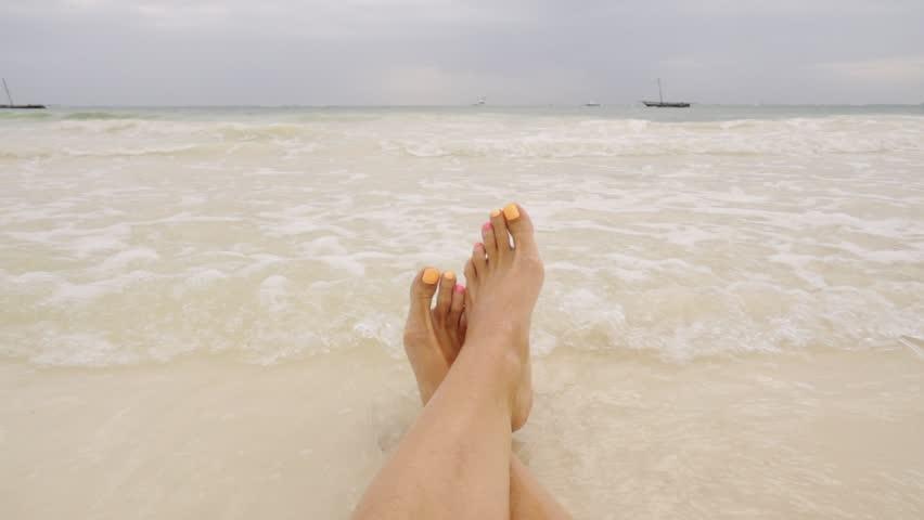 Woman in bikini lying on an ocen beach in slow motion