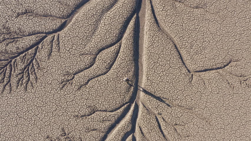 Climate change.Aerial zoom out view of a devastated farmer walking across the patterned cracked mud surface of a dry dam due to drought from climate change and global warming Royalty-Free Stock Footage #1025200034