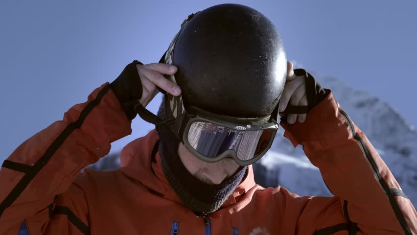 A professional rider puts on a helmet or hard hat. Getting ready to ski or snowboard. Enjoys winter sports. Behind the big snow-capped mountains. Royalty-Free Stock Footage #1025202806