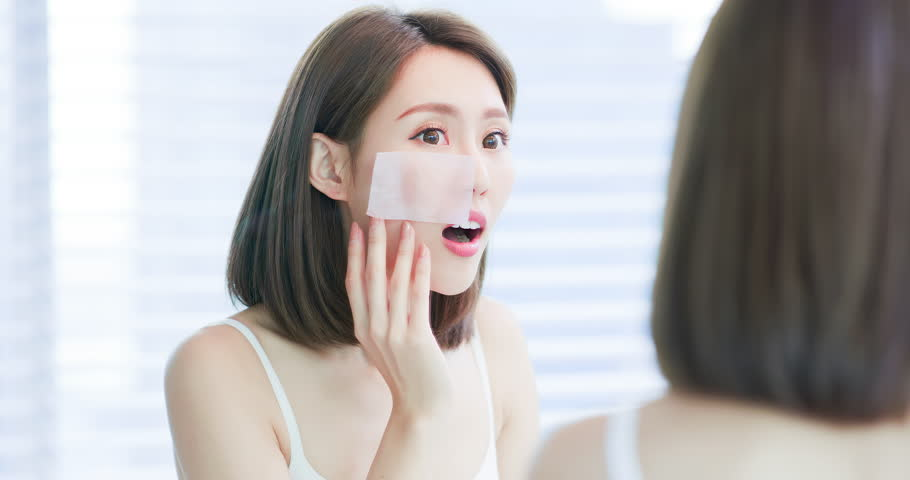 Young asian skin care woman upset after use oil blotting paper on her face | Shutterstock HD Video #1025204801