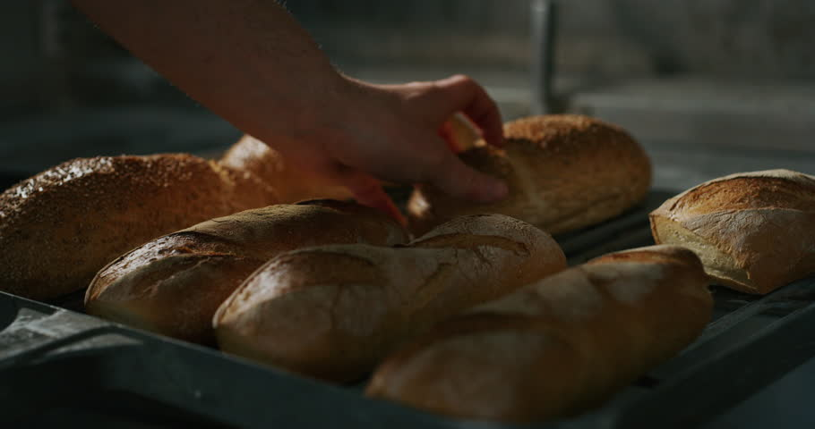 Slow motion close up of a baker pulling out from the oven warm fresh bread just made in a bakery. | Shutterstock HD Video #1025207198