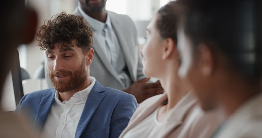 Attractive businessman chatting with colleagues in office meeting having conversation sharing ideas with diverse corporate group in workplace | Shutterstock HD Video #1025208512