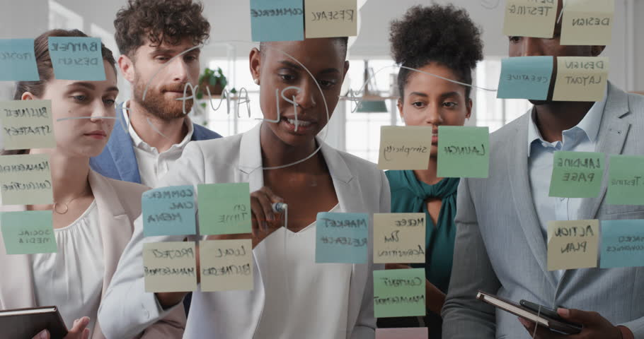 Corporate business people using sticky notes brainstorming problem solving strategy on glass whiteboard team leader woman showing solution for project deadline in office meeting | Shutterstock HD Video #1025208716