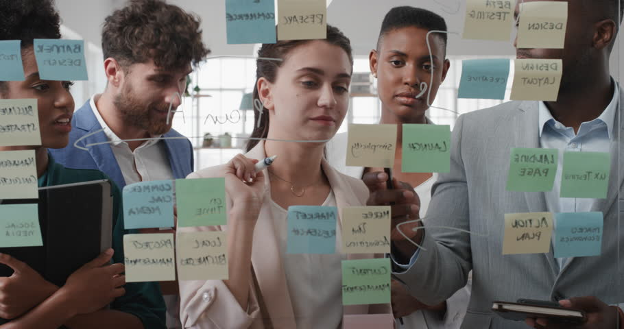 corporate business people using sticky notes brainstorming problem solving strategy on glass whiteboard team leader woman showing solution for project deadline in office meeting #1025208734