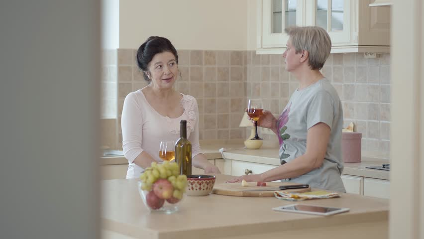 Two mature girlfriends met and chatting standing in the kitchen. Black-haired girl gesticulates and tells something to her friend. A gray-haired adult woman standing with a glass of wine. #1025235527