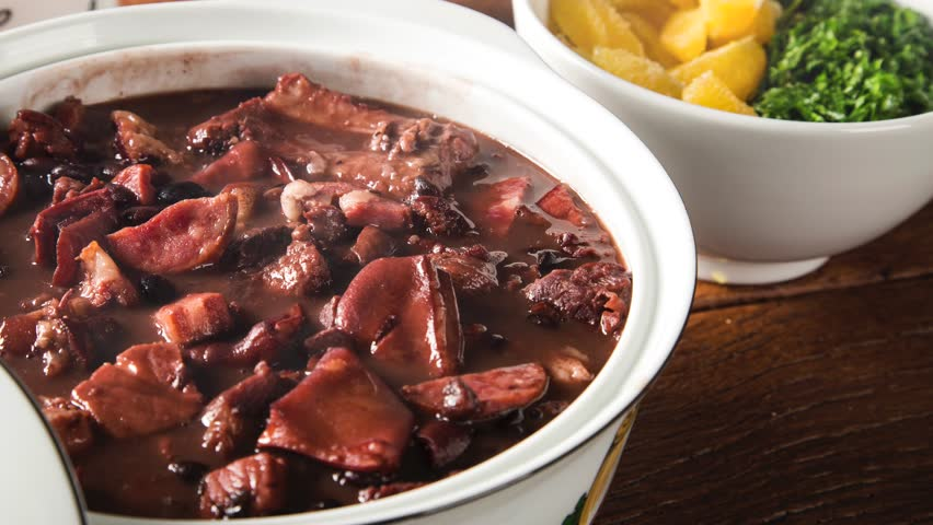 Delicious feijoada served in a white pot typical of Minas Gerais on a rustic wooden table accompanied by seasonings with smoke. Traditional Brazilian food.