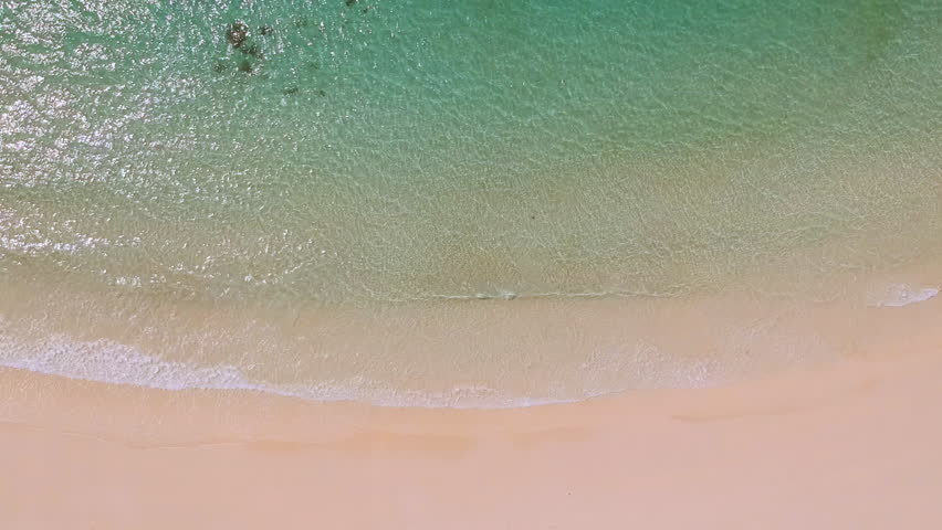 Aerial view of clear sand beach and sea. Ocean surface texture, Top view sea waves flying over tropical clear sandy beach and waves, background forie credit | Shutterstock HD Video #1025249009