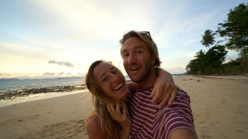 Couple take selfie portrait on beach in Thailand. People travel luxury vacations fun and cool attitude concept. Selfie point of view  | Shutterstock HD Video #1025256074