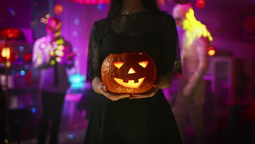 Halloween Costume Party: Gorgeous Witch Wearing Dress Holds Burning Pumpkin and Dances Seductively. Background: Beautiful She Devil, Scary Death, Count Dracula, Zombie Dancing in the Decorated Room | Shutterstock HD Video #1025264297