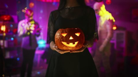 Halloween Costume Party: Gorgeous Witch Wearing Dress Holds Burning Pumpkin and Dances Seductively. Background: Beautiful She Devil, Scary Death, Count Dracula, Zombie Dancing in the Decorated Room