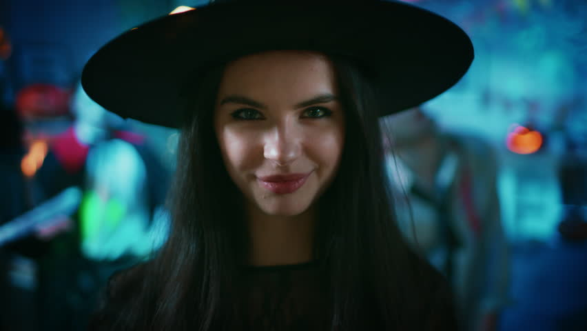 Halloween Costume Party. Zoom Out Close-up Portrait of Gorgeous Young Witch Wearing Dress and Hat Smiles seductively. Background: Colorful in the Decorated Room with Monsters Having Fun.Shot on 8K RED | Shutterstock HD Video #1025264447