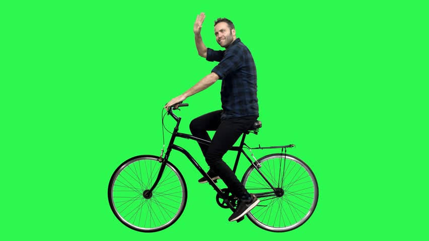 Cute man riding a bicycle over green screen, looking around and upwards, waving hello. No motion blur for optimal keying.