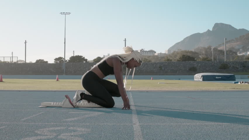 Side view of a female athlete starting her sprint on a running track. Runner taking off from the starting blocks on running track.