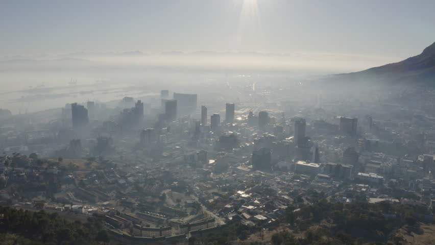 4K aerial view of smog and pollution hanging over Cape Town City centre, harbour and surrounding suburbs at sunrise