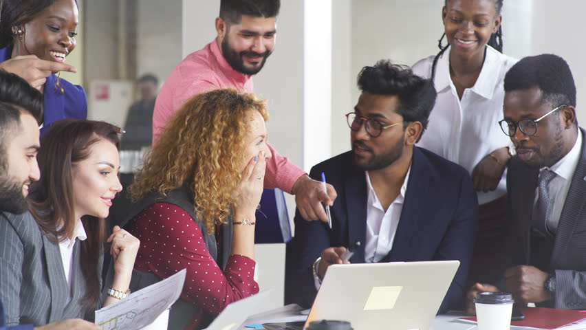 Searching of new insights and brilliant ideas. Mixed-race group of nine diverse people browsing net and looking through documents while sitting at the table in office Royalty-Free Stock Footage #1025276060