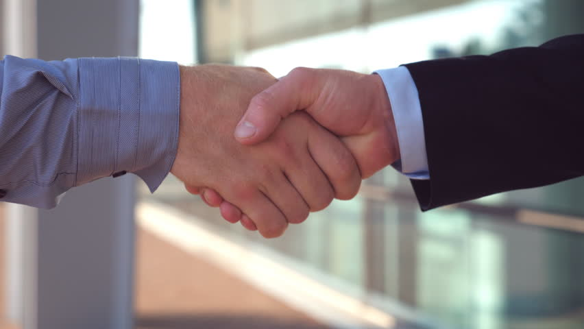 Close up of two successful businessmen greeting each other in urban environment. Young colleagues meeting and shaking hands near office building. Handshake of business partners outdoor. Side view #1025277068