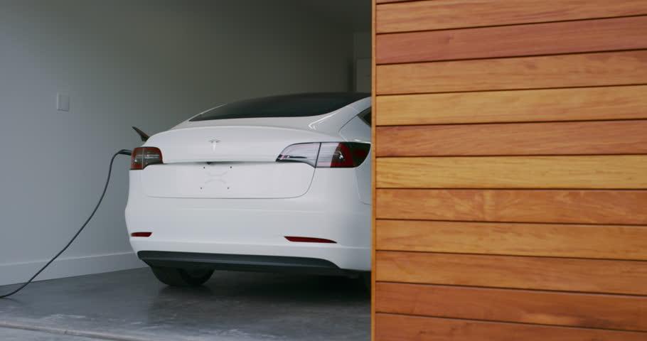 CALIFORNIA, USA - CIRCA MARCH 2019: Electric car charging in modern smart home garage, Tesla Model 3, modern electric vehicle