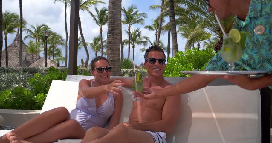 Couple Drinking Poolside on Bed With Tropical Drinks, Resort Pool