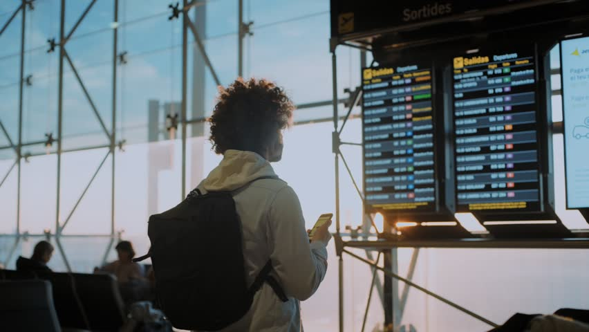 Funny casual looking and authentic young traveller with curly crazy hair studies flight information display in departure terminal of international or domestic airport, travel blogger inspiration