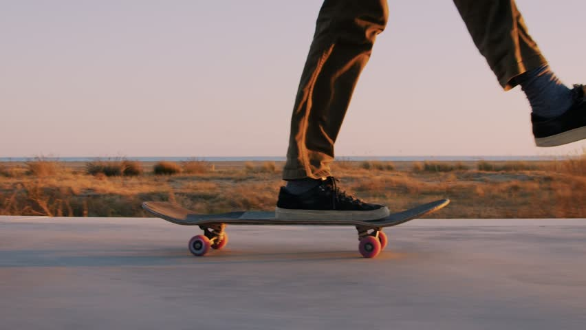 Slow motion cinematic close up of authentic and trendy skateboarder stroll through sunset filled california vibes promenade on warm summer evening. Outdoors activity. Dreamy teenage mood