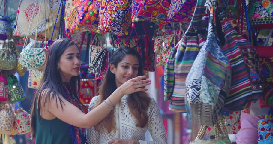4K Female friends chatting & shopping for handbags in Indian street market. Slow motion. Royalty-Free Stock Footage #1025311511