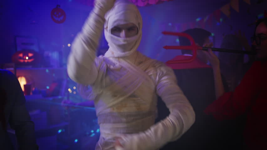 Halloween Costume Party: Old Skinny and Bandaged Mummy Dances. In the Background Zombie, Death, Witch and She Devil Have Fun in a Monster Party Decorated Room. Shot on 8K RED