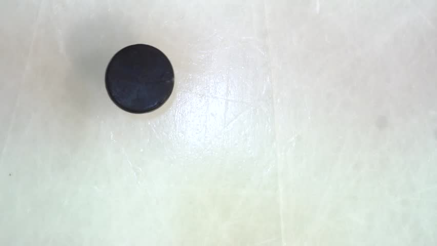 Hockey puck spins and falls on the ice in slow motion and stick hitting it, top view | Shutterstock HD Video #1025339459