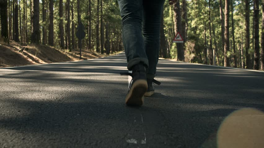 Follow camera shot of fashionable young hip man in urban adventurer outfit, blue jeans and black tshirt, walk casually on beautiful mountain road. COncept wanderlust blogger inspiration | Shutterstock HD Video #1025339918