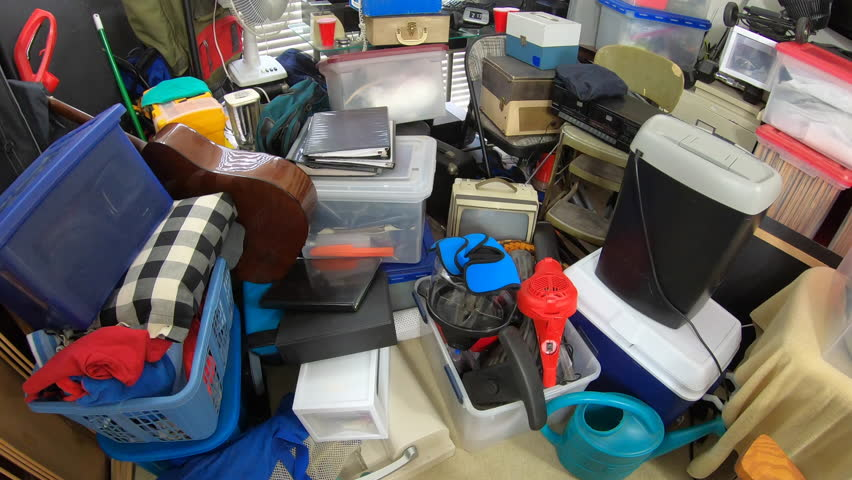 Cluttered hoarder room.  Slow dolly move over piles of household items, vintage electronics, business equipment and miscellaneous junk.   Shutterstock HD Video #1025355533