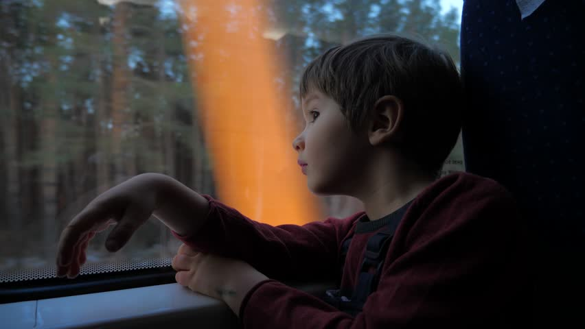 The boy stands at the train window and looks out the window at the running landscapes. Travel by train. Tourism on vacation, travel around the world. Kid traveling by train, dreaming about something.